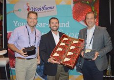Nick Wishnatzki, Marcus Caswell and James Peterson with Wish Farms proudly show a flat of strawberries and a 32 oz. clamshell of blueberries.