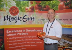 Tony Otto with MagicSun proudly shows tomatoes on the vine.
